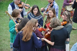 Shows a group of young teens delightedly playing the fiddle outdoors, on the grass. In the background, some adults play as well.