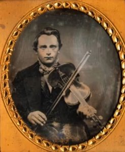 Ambrotype photograph of a young man playing the fiddle. Bound in a brown leather frame.