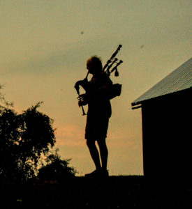 Silhouette of Pat O'Gorman waking the Algoma-Trad campers at dawn.