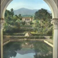 """Lantern slide from the Library of Congress Frances Benjamin Johnston Collection: """"Las Tejas,"""" Oakleigh Thorne house, 170 Picacho Road, Montecito, California. View from swimming pool pavilion to house."""