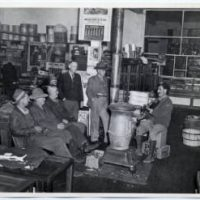 A man playing the fiddle in a country store in Tennessee in the 1940s. He sits next to a stove, a number of people sit or lean while giving him their undivided attention.