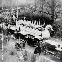 Toronto Santa Claus parade, 1919: Shows a swan float and lots of lovely old cars and people in festive witnter garb.