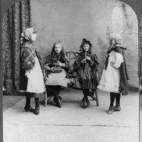 Shows four young women: an illeann piper, a whistle player and two young dancers from Cork, Ireland, in the 1800s.